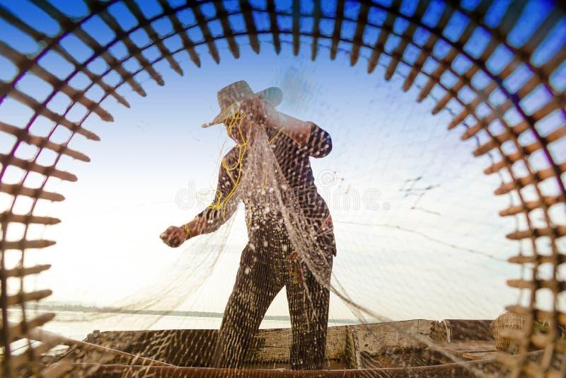 Ψαράς που ρίχνει το δίχτυ του ψαρέματος στη λίμνη Ψαράς με το fishi στοκ εικόνες