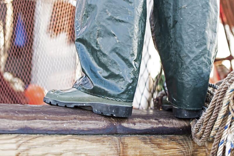 Ψαράς που στέκεται στην άκρη του ξύλινου σκάφους Πράσινες μπότες Fishermans με τα δίκτυα και σχοινιά στο υπόβαθρο στοκ φωτογραφίες