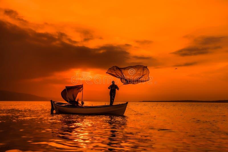 Ψαράς σκιαγραφιών στο αλιευτικό σκάφος που θέτει καθαρό με την ανατολή στοκ εικόνες