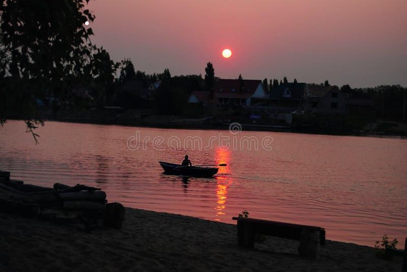 Ψαράς στη βάρκα στην ανατολή στοκ εικόνες