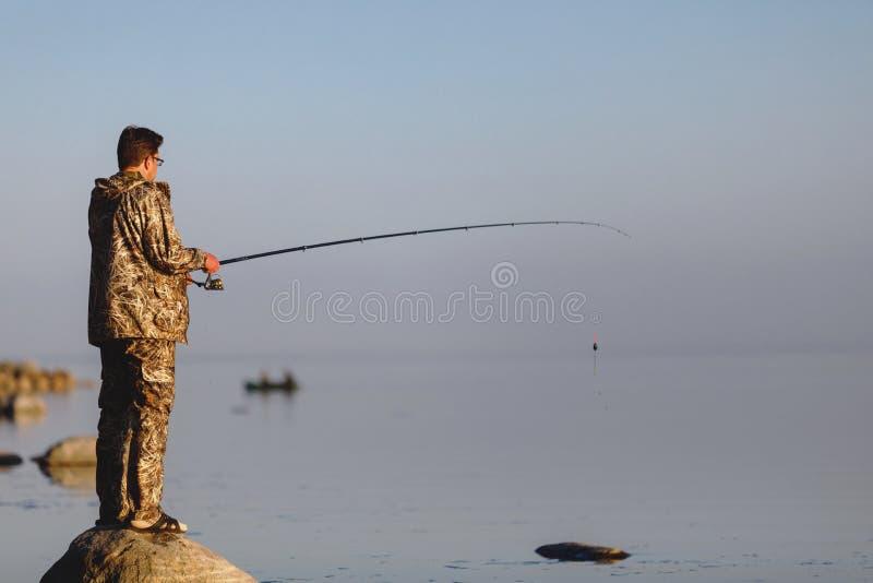 Ψαράς στη λίμνη στο ηλιοβασίλεμα με μια ράβδο αλιείας στοκ εικόνες με δικαίωμα ελεύθερης χρήσης