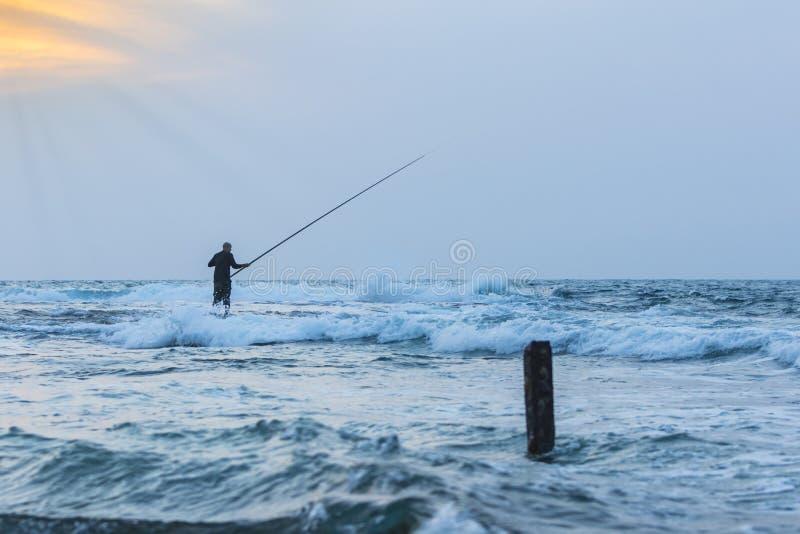 Ψαράς στο ηλιοβασίλεμα στα κυματιστά νερά στοκ φωτογραφία με δικαίωμα ελεύθερης χρήσης