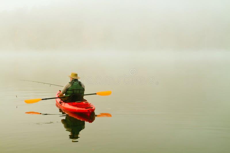 Ψαράς στο κόκκινο καγιάκ στοκ φωτογραφίες