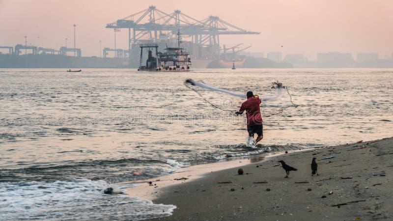 Ψαράς Kochi οχυρών που ρίχνει το δίχτυ του στο νερό Ινδία στοκ φωτογραφία