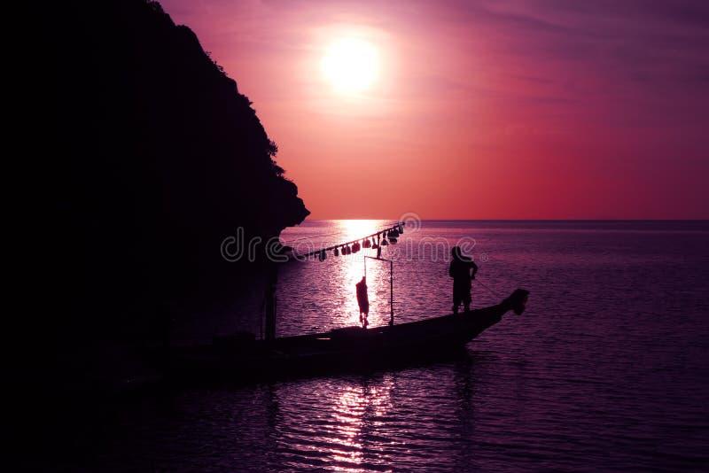 Ψαράδες με το αλιευτικό σκάφος θαλασσίως το βράδυ στοκ εικόνα με δικαίωμα ελεύθερης χρήσης