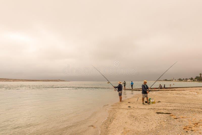 Ψαράδες στο ηλιοβασίλεμα στη λιμνοθάλασσα Langebaan στοκ εικόνα