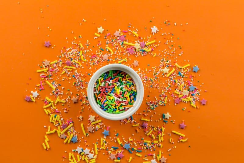 Ψεκάζει στο φωτεινό πορτοκαλί υπόβαθρο με λίγο άσπρο κύπελλο στη μέση του υποβάθρου και το πολύχρωμο κάλυμμα κέικ ψεκάζει στοκ φωτογραφία