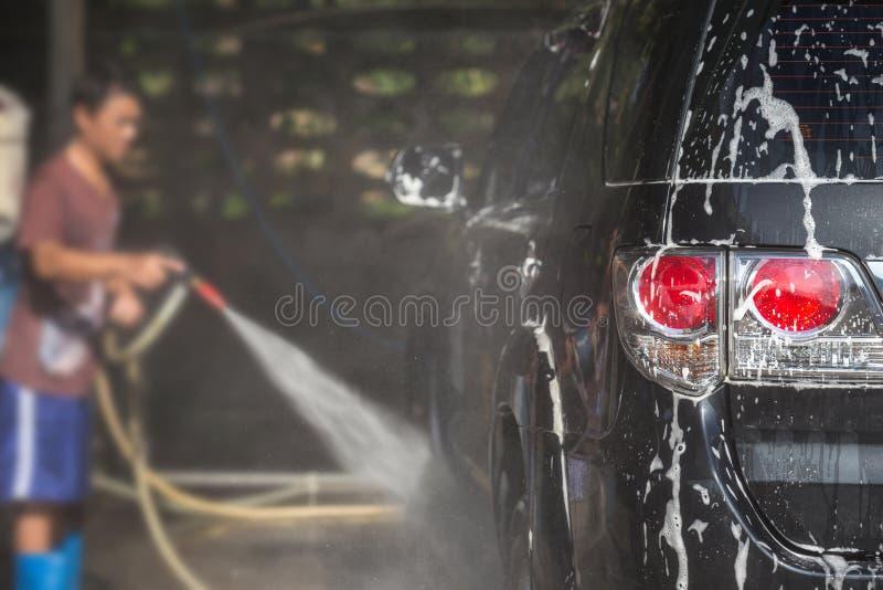 Ψεκάζοντας πλυντήριο πίεσης ατόμων για το πλύσιμο αυτοκινήτων στο κατάστημα προσοχής αυτοκινήτων Focu στοκ εικόνες με δικαίωμα ελεύθερης χρήσης