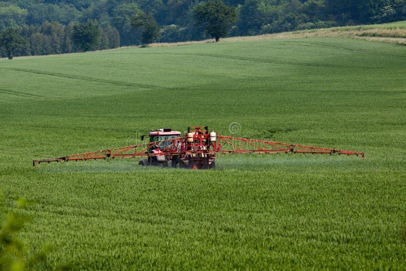 Ψεκάζοντας φυτοφάρμακα τρακτέρ στο μεγάλο πράσινο τομέα στοκ εικόνες με δικαίωμα ελεύθερης χρήσης