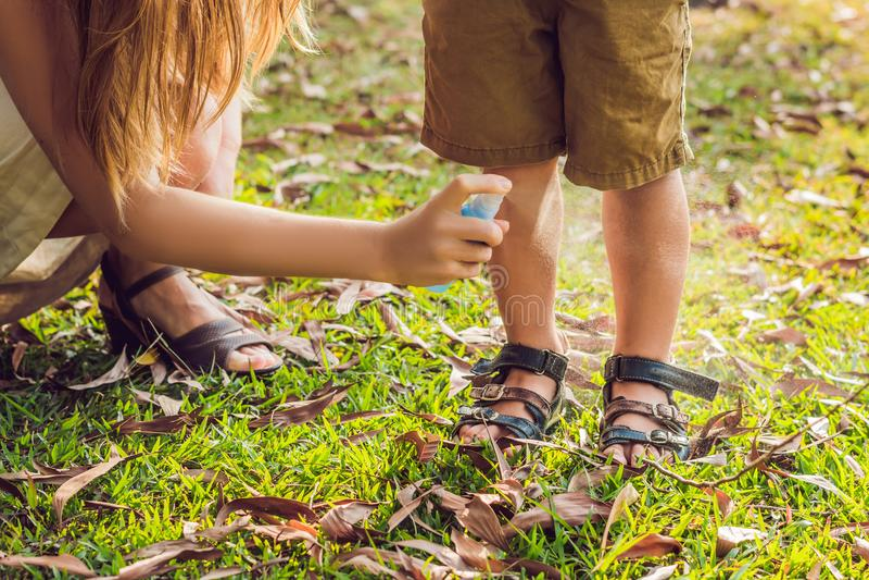Ψεκασμός κουνουπιών χρήσης Mom και γιων Ψεκάζοντας απωθητική ουσία εντόμων στο δέρμα στοκ εικόνες