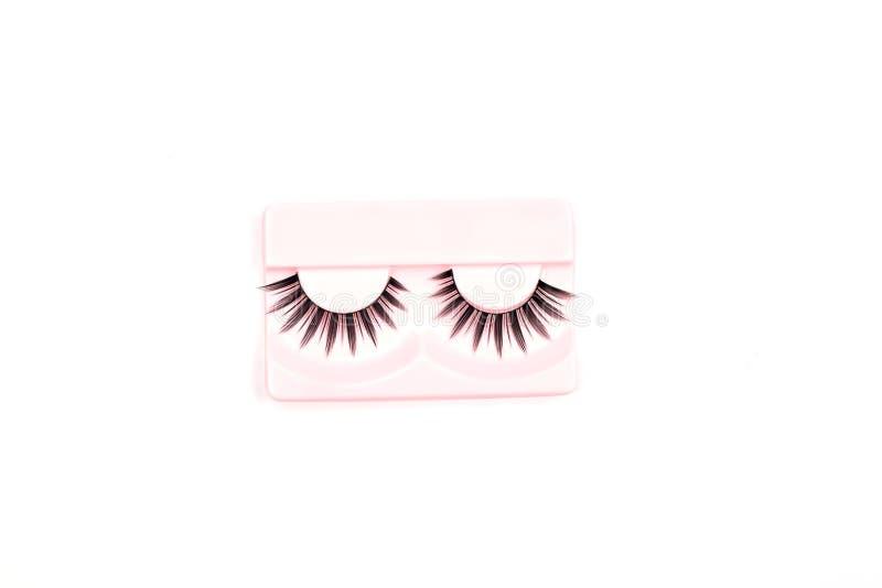 Ψεύτικα eyelashes που απομονώνονται στην άσπρη ανασκόπηση Επίπεδος-βάλτε, τοπ άποψη διάστημα αντιγράφων για το κείμενό σας στοκ εικόνα