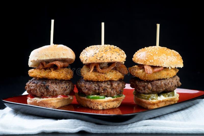 Ψηλά μίνι burgers βόειου κρέατος ολισθαινόντων ρυθμιστών που μοιράζονται τα τρόφιμα στοκ εικόνες