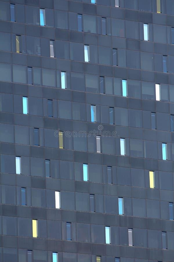 Ψηλά στενά ζωηρόχρωμα παράθυρα στο νέο σκοτεινό σύγχρονο υπόβαθρο σύστασης κτιρίου γραφείων στοκ εικόνες