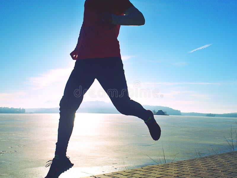 Ψηλή παραλία ατόμων που τρέχει στην ανατολή, παγωμένη ακτή λιμνών στοκ φωτογραφίες με δικαίωμα ελεύθερης χρήσης