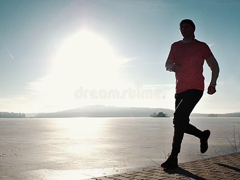 Ψηλή παραλία ατόμων που τρέχει στην ανατολή, παγωμένη ακτή λιμνών στοκ εικόνες με δικαίωμα ελεύθερης χρήσης