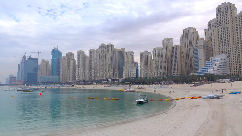 Ψηλοί ουρανοξύστες ενός σύγχρονου, μητροπολιτικού πύργου εικονικής παράστασης πόλης πέρα από μια όμορφη, άσπρη, αμμώδη παραλία μι στοκ εικόνες
