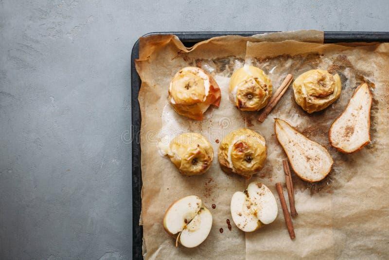 Ψημένα αχλάδια και μήλα στο τηγάνι ψησίματος με τα καρυκεύματα, τις μικρά κολοκύθες και τα λουλούδια γύρω στον γκρίζο πίνακα στοκ εικόνες