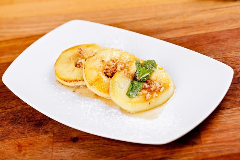 Ψημένα δαχτυλίδια μήλων με τα ξύλα καρυδιάς και μέλι στο άσπρο πιάτο Επιδόρπιο φθινοπώρου στοκ φωτογραφία με δικαίωμα ελεύθερης χρήσης