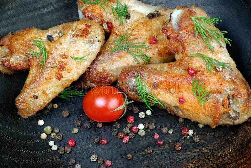 Ψημένα κοτόπουλο φτερά στο ξύλινο υπόβαθρο φτερά κοτόπουλου, ντομάτες και μίγμα πιπεριών, κινηματογράφηση σε πρώτο πλάνο στοκ φωτογραφία με δικαίωμα ελεύθερης χρήσης