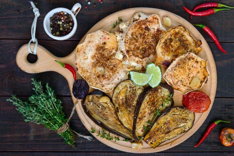 Ψημένα λαχανικά: μελιτζάνα, patisson, ντομάτες σε μια στρογγυλή ξύλινη στάση σε ένα σκοτεινό υπόβαθρο στοκ εικόνες με δικαίωμα ελεύθερης χρήσης