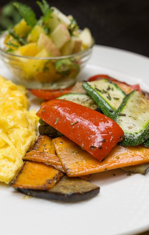 Ψημένα λαχανικά στο άσπρο πιάτο: τεμαχισμένα καρότα, πιπέρι κουδουνιών, κολοκύθια με τα ανακατωμένα αυγά και θολωμένη σαλάτα μήλω στοκ φωτογραφία με δικαίωμα ελεύθερης χρήσης