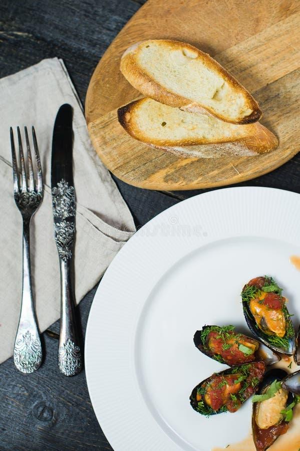 Ψημένα μύδια στη σάλτσα ντοματών με το κορίανδρο και την παρμεζάνα σε ένα άσπρο πιάτο στοκ εικόνες