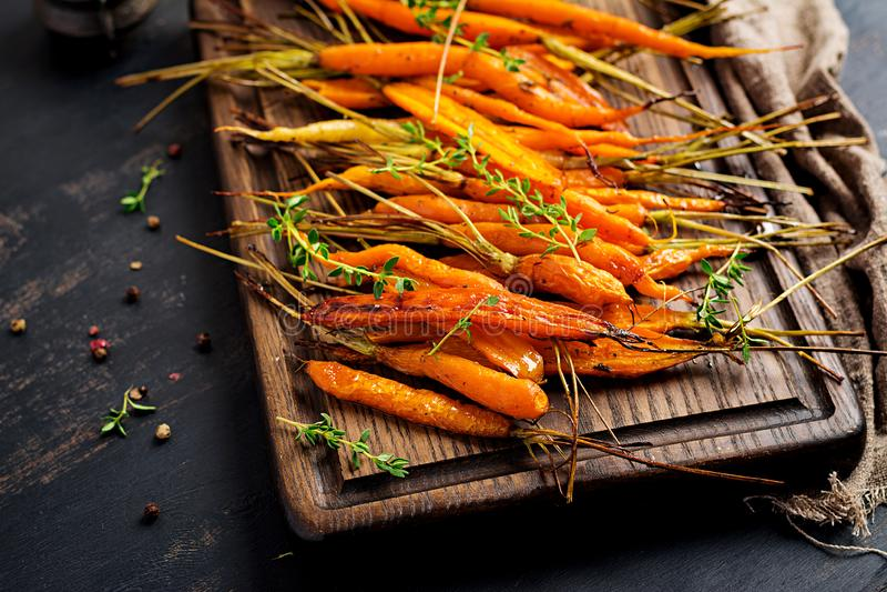 Ψημένα οργανικά καρότα με το θυμάρι, το μέλι και το λεμόνι Οργανικός vegan τα οργανικά καρότα με το θυμάρι, το μέλι και το λεμόνι στοκ εικόνα