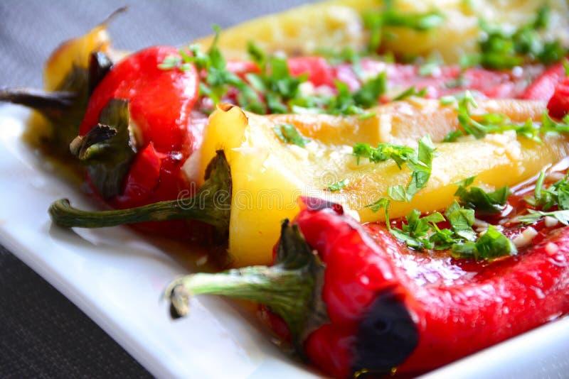 Ψημένα πιπέρια που εξυπηρετούνται στο άσπρο πιάτο στοκ εικόνες