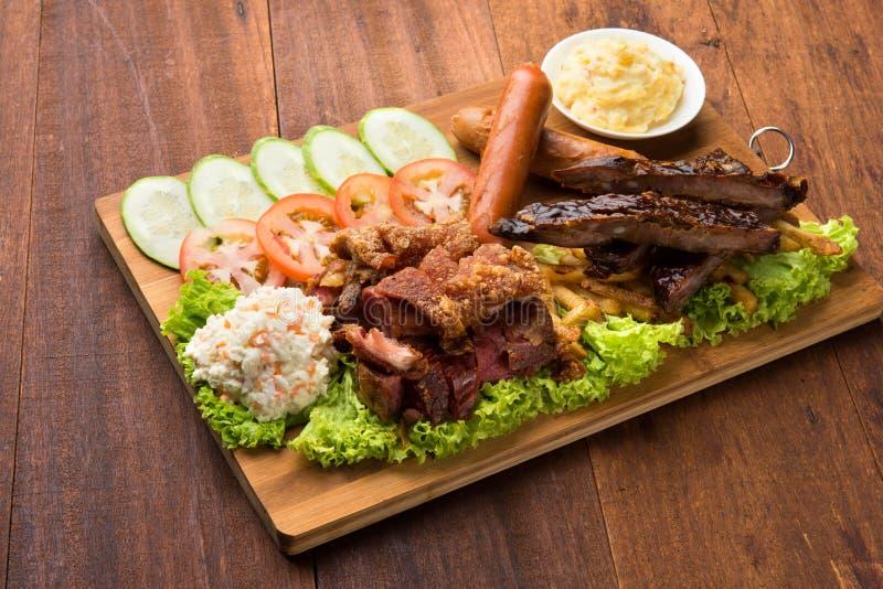 Ψημένα πλευρά αρθρώσεων χοιρινού κρέατος, πατάτες λουκάνικων και πολτοποίησης στοκ φωτογραφία με δικαίωμα ελεύθερης χρήσης
