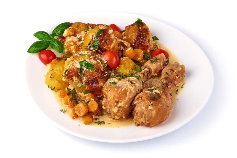 Ψημένα πόδια κοτόπουλου με τις ψημένα πατάτες και τα λαχανικά, που απομονώνονται στο άσπρο υπόβαθρο στοκ φωτογραφία