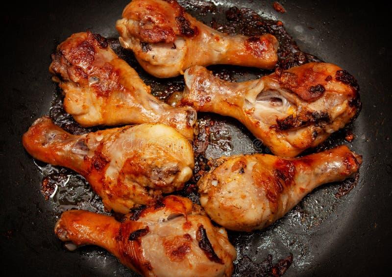 Ψημένα πόδια κοτόπουλου σε ένα μαύρο τηγάνι στοκ εικόνες