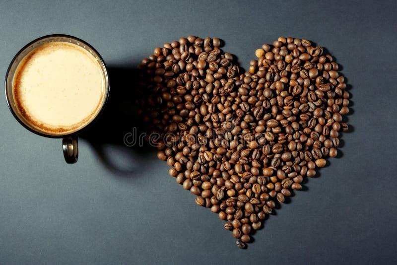 Ψημένα σιτάρια με μορφή μιας καρδιάς και ενός φλυτζανιού του αρωματικού καφέ σε έναν πίνακα στοκ εικόνα με δικαίωμα ελεύθερης χρήσης