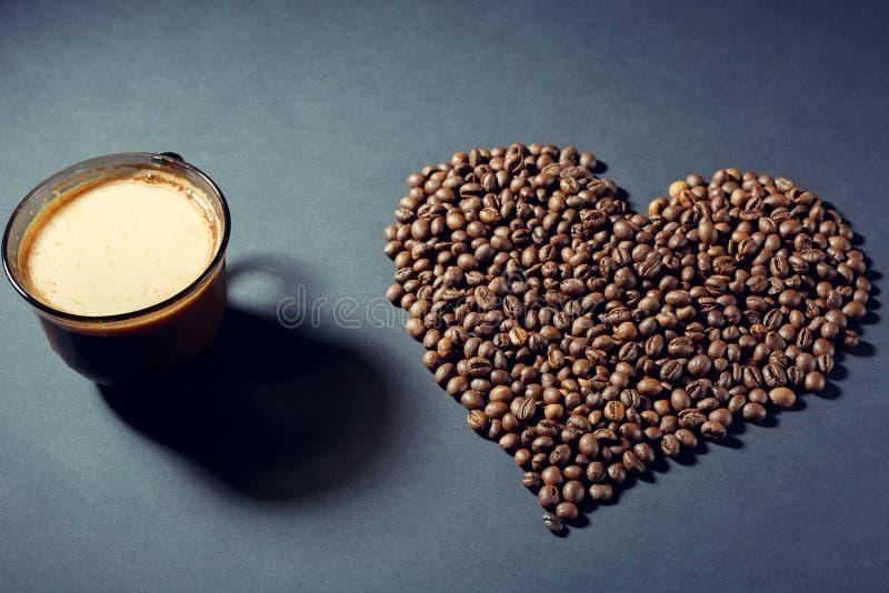 Ψημένα σιτάρια με μορφή μιας καρδιάς και ενός φλυτζανιού του αρωματικού καφέ σε έναν πίνακα στοκ φωτογραφία με δικαίωμα ελεύθερης χρήσης