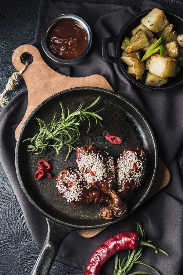 Ψημένα στη σχάρα αντικνήμια κοτόπουλου στη σάλτσα ντοματών με το πιπέρι τσίλι σκοτεινές παν και ψημένες πατάτες σε ένα κύπελλο στοκ φωτογραφίες με δικαίωμα ελεύθερης χρήσης