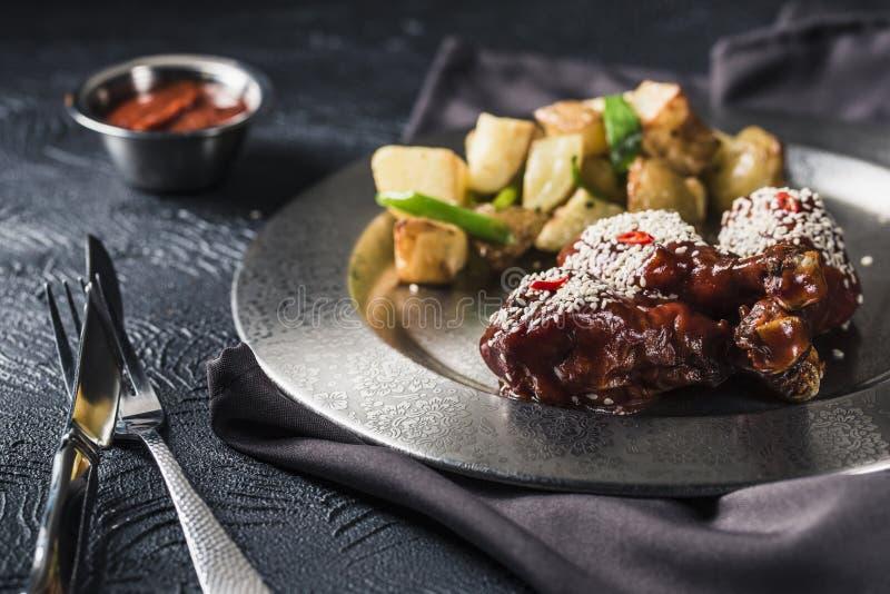 Ψημένα στη σχάρα αντικνήμια κοτόπουλου στη σάλτσα ντοματών με το πιπέρι τσίλι και τις ψημένες πατάτες στοκ φωτογραφία με δικαίωμα ελεύθερης χρήσης
