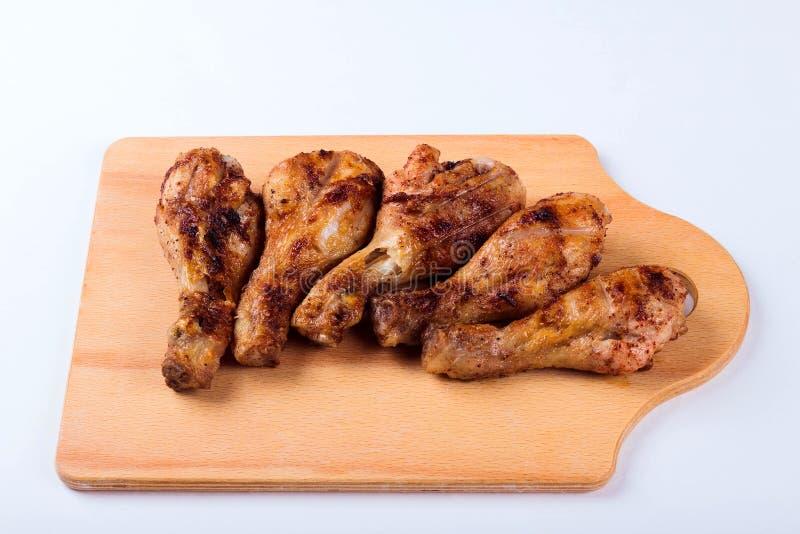 Ψημένα στη σχάρα αντικνήμια κοτόπουλου σε έναν ξύλινο δίσκο στοκ εικόνα