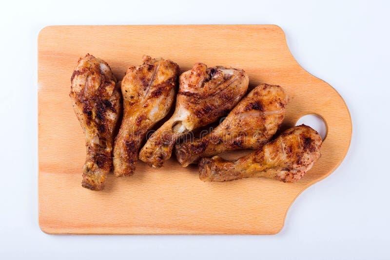 Ψημένα στη σχάρα αντικνήμια κοτόπουλου σε έναν ξύλινο δίσκο στοκ εικόνες