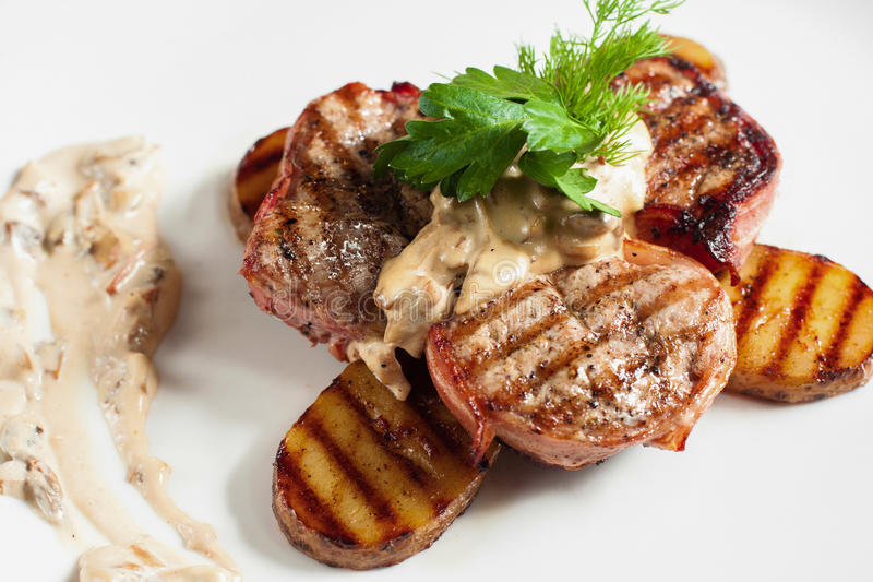 Ψημένα στη σχάρα καταστήματα χοιρινού κρέατος με την πατάτα στο άσπρο πιάτο στοκ φωτογραφία με δικαίωμα ελεύθερης χρήσης