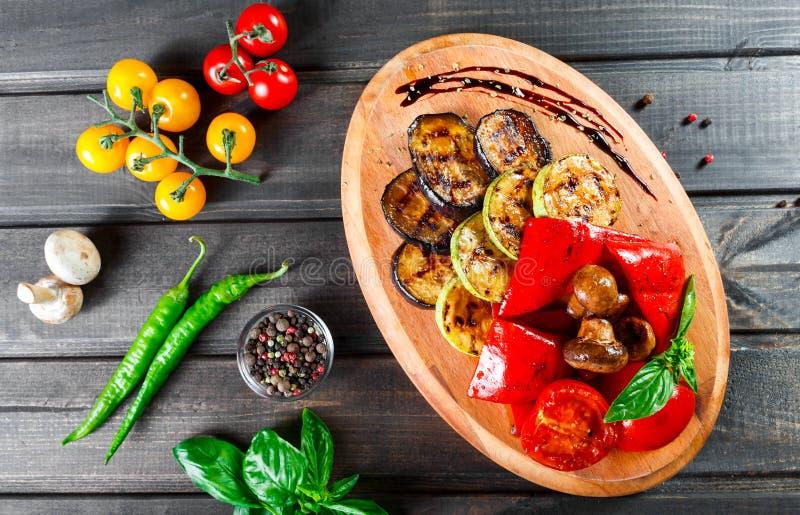 Ψημένα στη σχάρα λαχανικά, μανιτάρια, ντομάτες, μελιτζάνα, πιπέρι στον τέμνοντα πίνακα στοκ φωτογραφία