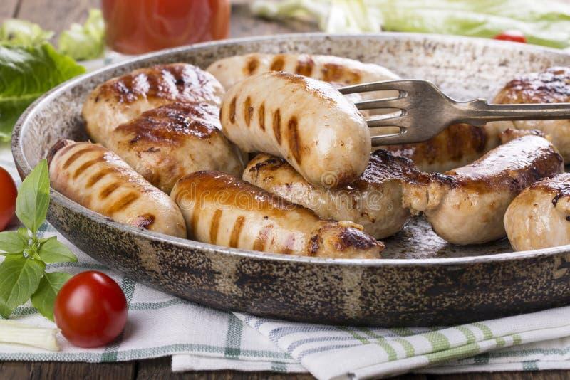 Ψημένα στη σχάρα λουκάνικα και burgers κοτόπουλου στοκ εικόνες