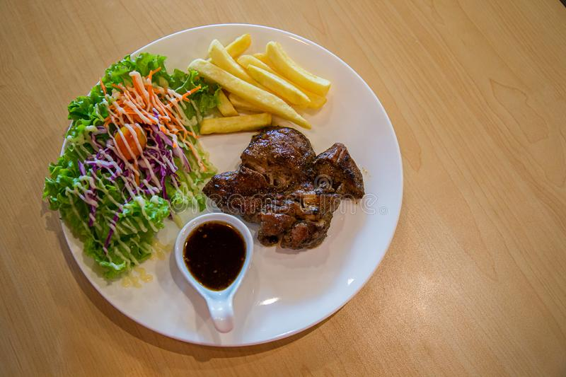 Ψημένα στη σχάρα μπριζόλα και λαχανικά χοιρινού κρέατος πιάτο του ψημένου στη σχάρα χοιρινού κρέατος με τις τηγανιτές πατάτες και στοκ φωτογραφίες