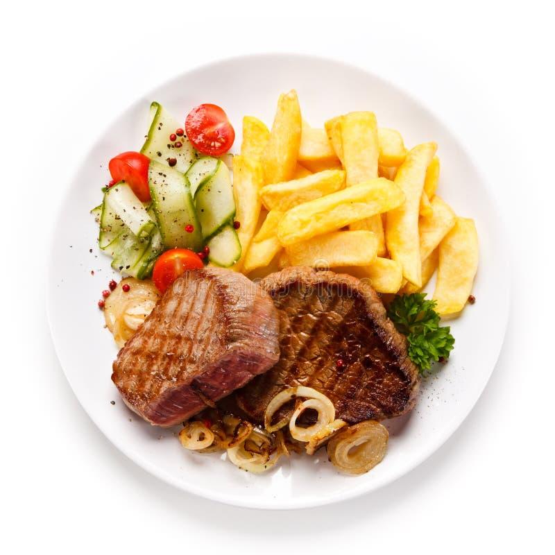 Ψημένα στη σχάρα μπριζόλες, τηγανιτές πατάτες και λαχανικά στοκ φωτογραφία