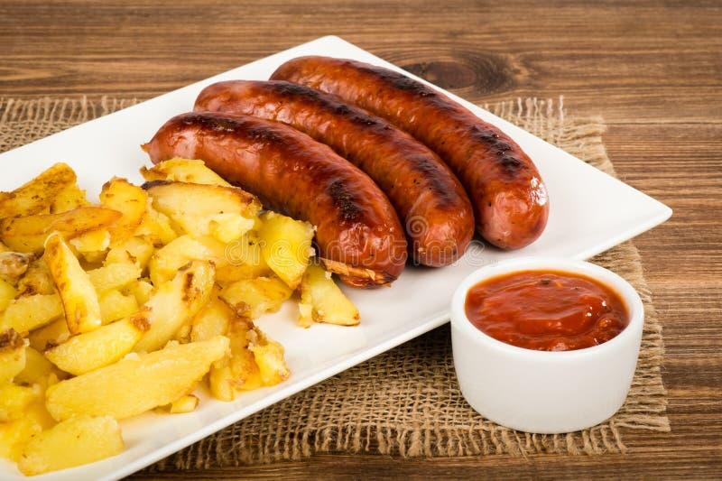 Ψημένα στη σχάρα λουκάνικα και τηγανισμένες πατάτες στο άσπρο πιάτο στην αγροτική επιφάνεια στοκ εικόνα με δικαίωμα ελεύθερης χρήσης