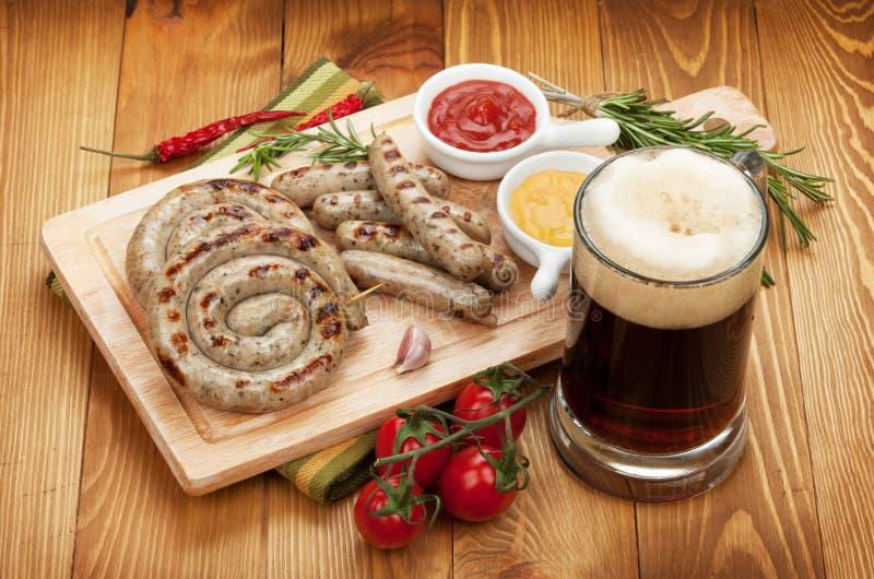 Ψημένα στη σχάρα λουκάνικα με την κούπα της μπύρας στοκ φωτογραφίες με δικαίωμα ελεύθερης χρήσης