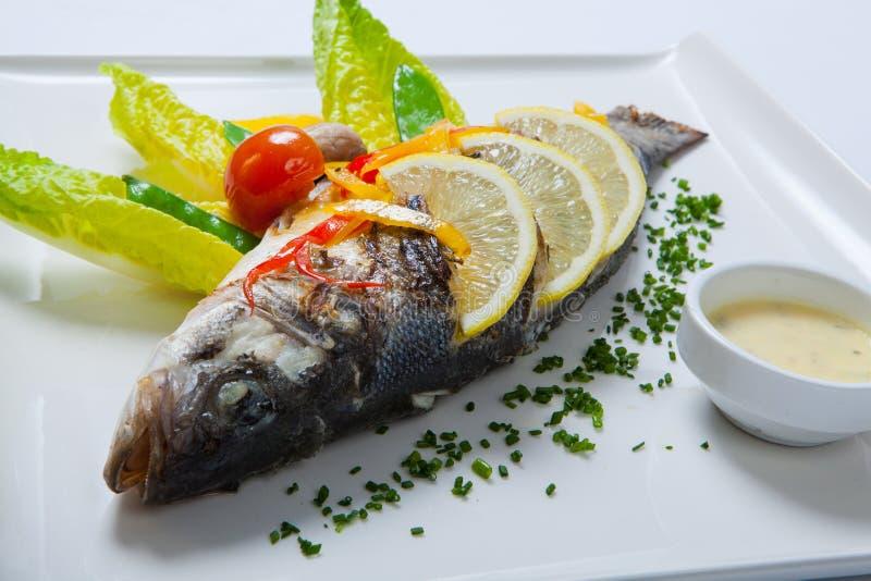 Ψημένα στη σχάρα ολόκληρα τα ψάρια διακόσμησαν με τα φύλλα της ντομάτας μαρουλιού και κερασιών, που εξυπηρετήθηκαν με τη σάλτσα σ στοκ φωτογραφία με δικαίωμα ελεύθερης χρήσης