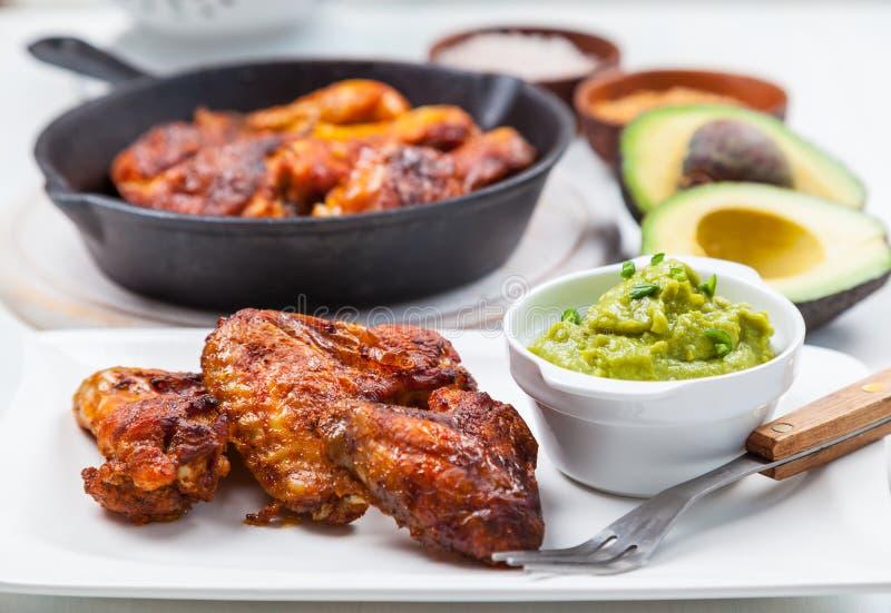 Ψημένα στη σχάρα πόδια και φτερά κοτόπουλου με το guacamole στοκ φωτογραφίες