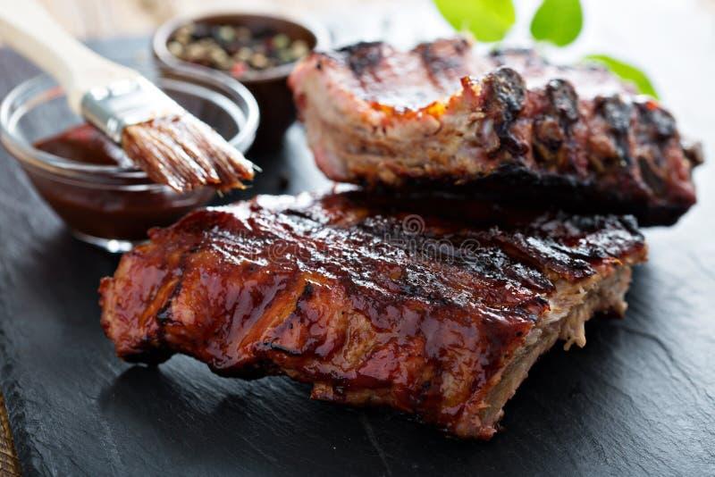 Ψημένα στη σχάρα πλευρά μωρών χοιρινού κρέατος με bbq τη σάλτσα στοκ φωτογραφία