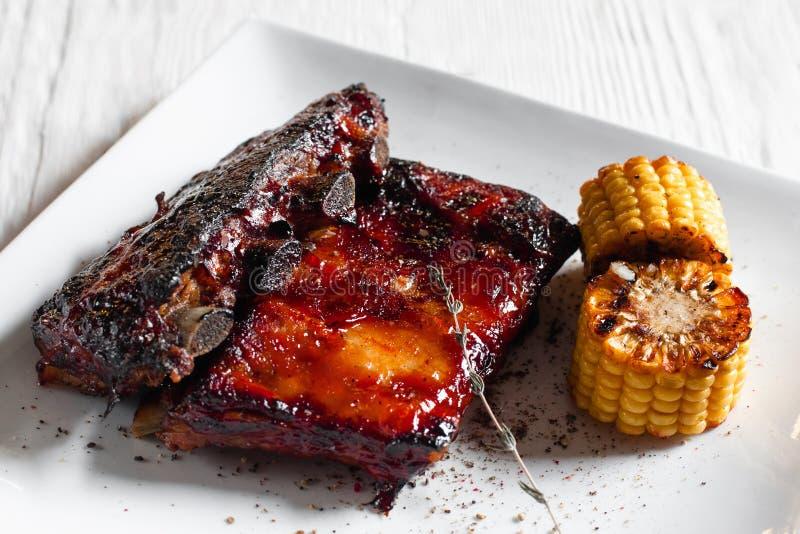 Ψημένα στη σχάρα πλευρά χοιρινού κρέατος με το καλαμπόκι στο άσπρο πιάτο στοκ εικόνα με δικαίωμα ελεύθερης χρήσης