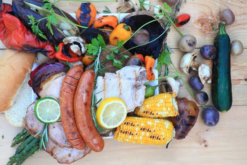 Ψημένα στη σχάρα τρόφιμα στη σχάρα πυρκαγιάς στρατόπεδων πέρα από τον ξύλινο πίνακα στοκ εικόνες