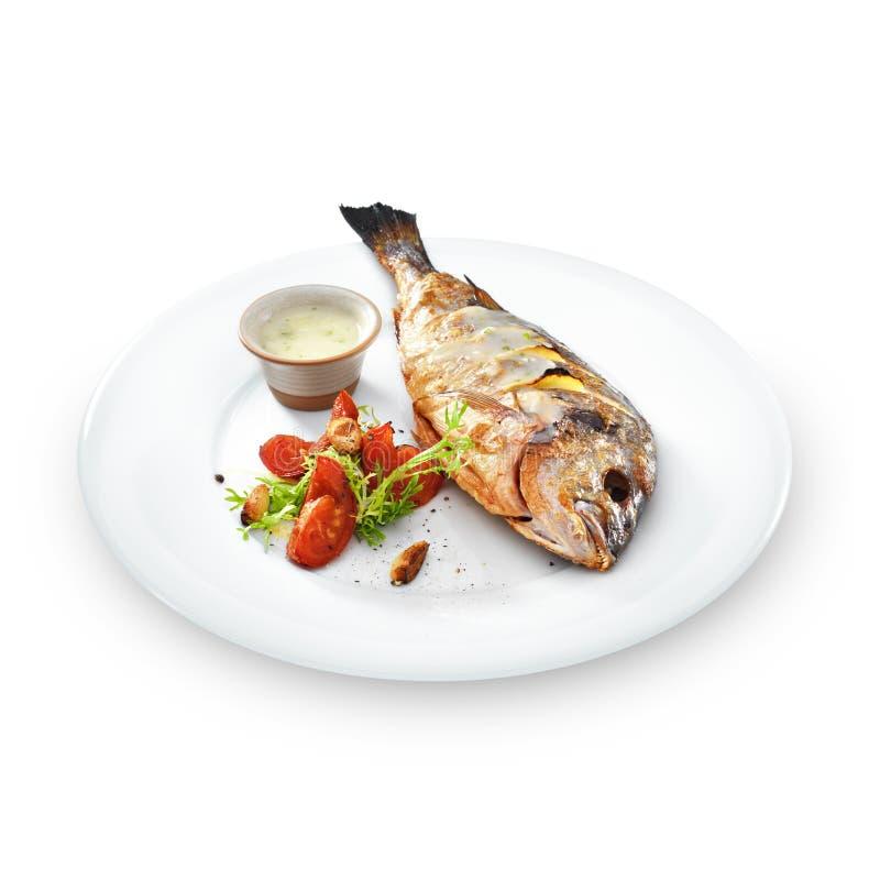 Ψημένα στη σχάρα υγιή ψάρια dorado με τα λαχανικά σε ένα στρογγυλό πιάτο στοκ εικόνες